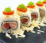 Разрезаем рулет на кусочки и оформляем блюдо помидорами и тобико. Подаем на стол.