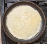 Поставьте на плиту на средний огонь и готовьте около 1 минуты. Низ блина должен стать слегка коричневого цвета.